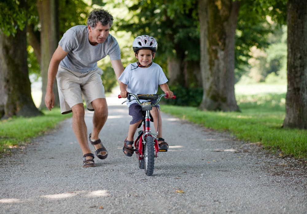 man teaching boy to ride a bike