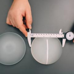 Hands measuring a breast implant