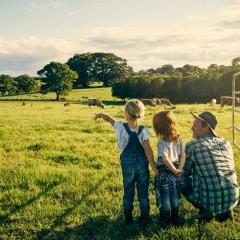 father and two daughters looking over farm