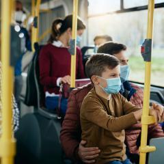 Man and boy on bus wearing masks