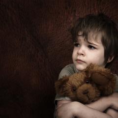 child hugging bear looking sad