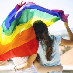 women hugging and holding a rainbow flag