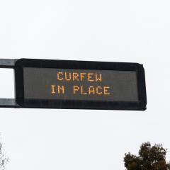 Road sign saying 'curfew in place'