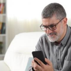 man sitting on couch scrolling through phone