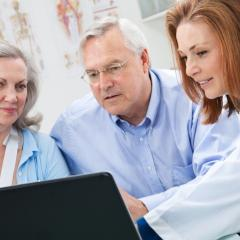 doctor and patients looking at laptop