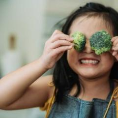 girl playing with broccoli covering her eyes