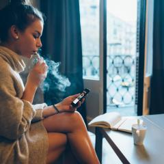 young woman on phone vaping