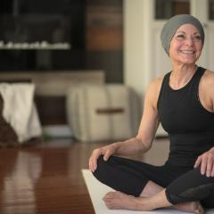 Woman smiling, sittinng on a yoga mat wearing a beanie hat