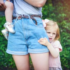 daughter hiding behind mother's leg