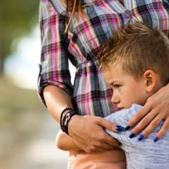 young boy hugging mother