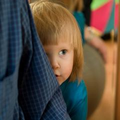young child hiding behind adult