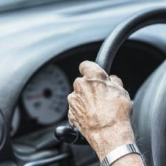 aged hands on a steering wheel