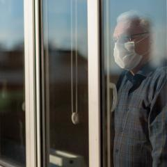 Older man with mask on at window