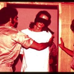 Guards with a blindfolded prisoner in the Stanford Prison Experiment, 1971